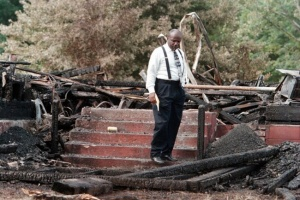 Older black man in a white shirt with suspenders and black slacks stands in front of red stairs where with burned rubble surrounding the area.
