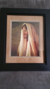the distance with his head and body covered in a light-colored cloth. This picture is matted with tan and in a thick black frame. The frame is against a grey background.