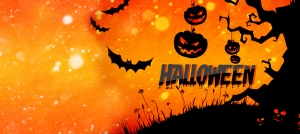 There is an orange background with a black spooky tree on top of a hill with pumpkins hanging from the tree limbs. 3 bats are pictured flying around. The text reads HALLOWEEN