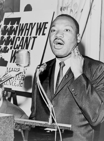 "Photograph of Martin Luther King JR at a press conference, standing at a podium behind microphones and speaking, 1964. Text Reads ""Why Can't W[ait]"""